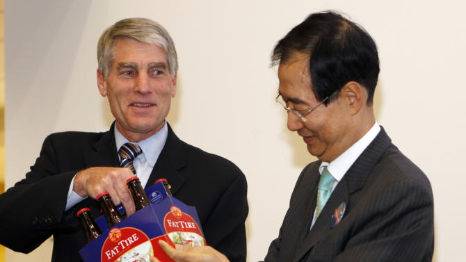 U.S. Senator Mark Udall, D-Colo., presents South Korean Ambassador Han Duk-Soo with a six-pack of Fat Tire beer at an Agriculture Trade Roundtable in Denver on Wednesday, April 20, 2011.  South Korea's ambassador to the U.S. was visiting Denver on Wednesday as part of efforts to promote a pending free trade agreement between his country and the U.S. He spoke at a luncheon hosted by the Metro Denver Economic Development Corp. He also was participating in an afternoon roundtable with Sen. Mark Udall, D-Colo., and Colorado Agriculture Commissioner John Salazar about how Colorado businesses might benefit from improved access to Korean markets.  (AP Photo/Ed Andrieski)