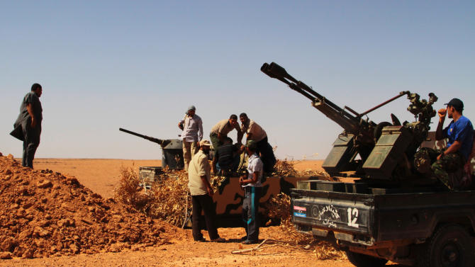 Rebel  fighters take control of  a military vehicle, centre, positioned to defend what used to be Gadhafi's 32nd infantry regiment's base at Mardun, some 10 kilometers from the outskirts of Ban Walid, Libya, Wednesday, Sept. 7, 2011. (AP Photo/Gaia Anderson)