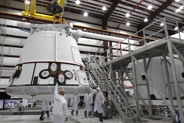 In this Nov. 16, 2011, photo provided by NASA, the SpaceX Dragon capsule is lifted to be placed atop its cargo ring inside a processing hangar at Cape Canaveral Air Force Station in Florida. The first