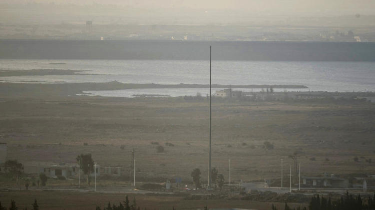 A bare flag pole is seen in Syria close to the border fence with the Israeli-occupied Golan Heights