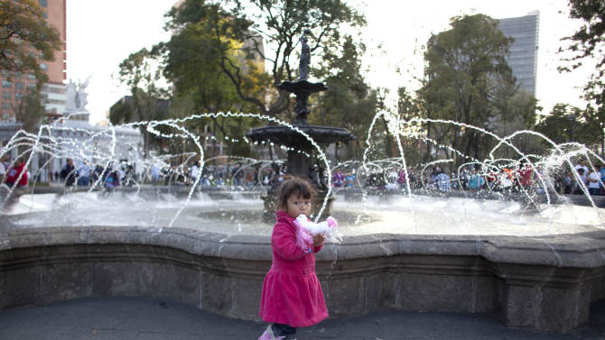Angy Saraui, 2, holds her toy pony as she walks in front a fountain at Alameda Central in Mexico City, Wednesday, Dec. 26, 2012. Made iconic in the Diego Rivera mural ìDream of a Sunday Afternoon in the Alameda,î some of the park's concrete sidewalks were replaced by marble, and makeshift vendor stands were kicked out. Mexico City's government is trying to transform one of the world's largest cities by beautifying public spaces, parks and monuments buried beneath a sea of honking cars, street hawkers, billboards and grime following decades of dizzying urban growth. (AP Photo/Alexandre Meneghini)