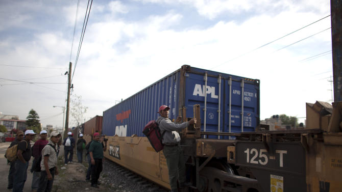 In this May 17, 2012 photo, migrants, mostly from Honduras, wait for a train going north in Lecheria, on the outskirts of Mexico City. While the number of Mexicans heading to the U.S. has dropped dramatically, a surge of Central American migrants is making the 1,000-mile northbound journey this year, fueled in large part by the rising violence brought by the spread of Mexican drug cartels. (AP Photo/Alexandre Meneghini)