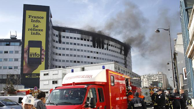 Police officers and rescue worker stand by the burning state radio headquarters, known as Maison de la Radio, in Paris, France, Friday, Oct.31, 2014. The massive building was undergoing renovations when the fire began. (AP Photo/Thibault Camus)