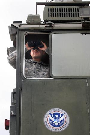 In this April 19, 2011 photo, Texas National Guardsman Cpl. Martinez surveys the terrain from a Border Patrol Skybox  near the Hidalgo International Bridge in Hidalgo, Texas.    The National Guard troops have augmented the Border Patrol's 21,000 agents by almost 6 percent since July, 2010. The troops serve as lookouts but are not directly involved in actual law enforcement activities. They are credited with helping arrest 17,000 illegal immigrants, almost 6 percent of those caught, according to Customs and Border Protection.(AP Photo/Delcia Lopez)