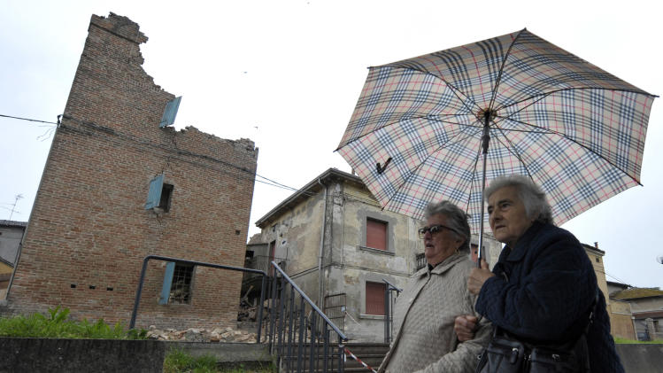 Two women walk past damaged buildings in San Felice Panaro, northern Italy, Sunday, May 20, 2012. A magnitude-6.0 earthquake shook northern Italy early Sunday. The quake struck at 4:04 a.m. Sunday between Modena and Mantova, about 35 kilometers (22 miles) north-northwest of Bologna at a relatively shallow depth of 10 kilometers (6 miles), the U.S. Geological Survey said. (AP Photo/Marco Vasini)