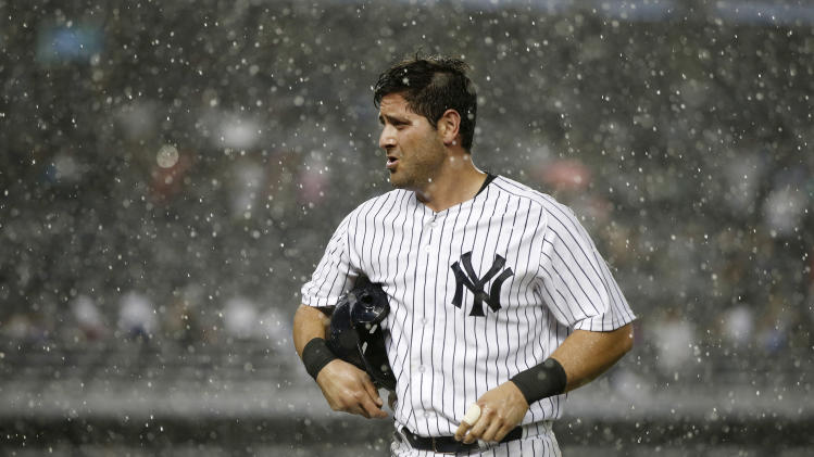 New York Yankees Francisco Cervell, who had been on second base, runs off the field after a sudden heavy rainstorm interrupted the fifth inning of a baseball game against the Texas Rangers at Yankee Stadium in New York, Wednesday, July 23, 2014. (AP Photo)