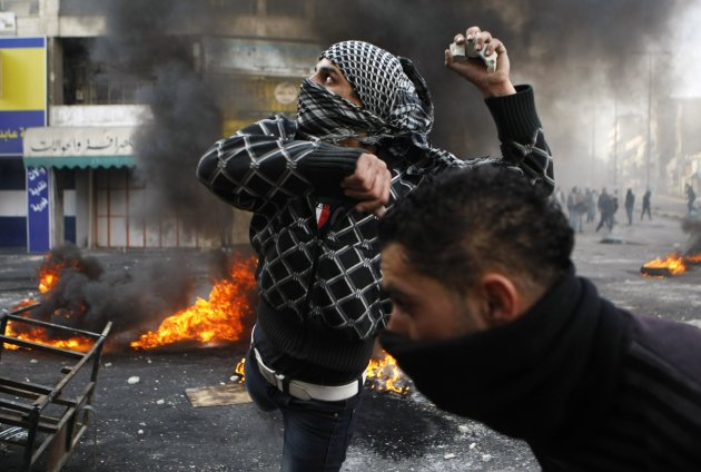 A Palestinian protester throws stones during clashes with Israeli soldiers in Hebron following the funeral of Palestinian prisoner Jaradat