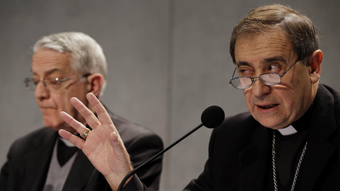Bishop Juan Ignacio Arrieta, right, flanked by Vatican spokesman, Rev. Federico Lombardi gestures during a press conference at the Vatican, Friday, Feb. 22, 2013. Pope Benedict XVI may enact a new law governing the upcoming conclave to elect a new pope amid continued uncertainty over when the voting can begin. Lombardi, said Wednesday that he didn't know for sure if the new law under consideration would address the timing of the conclave following Benedict's Feb. 28 resignation. (AP Photo/Gregorio Borgia)