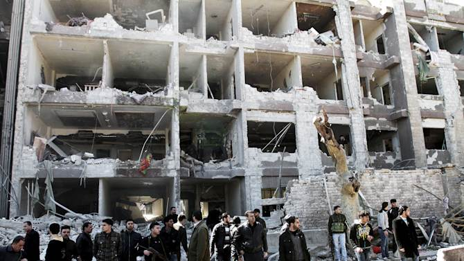 FILE - In this Saturday, March 17, 2012 file photo, Syrian security officers gather in front the damaged building of the aviation intelligence department, which was attacked by one of two explosions in Damascus, Syria. A new al-Qaida-style group claimed Wednesday, March 21, 2012 that it carried out the double suicide bombing that killed dozens. Foreign Islamic militants fighting Syria's regime pose a dilemma for the country's rebels, and nothing typifies the problem more than Jabhat al-Nusra, a shadowy group of veterans of jihad in Iraq, Libya and elsewhere. Some rebels worry the group is too radical, using al-Qaida-style tactics of suicide bombings. (AP Photo/Bassem Tellawi, File)