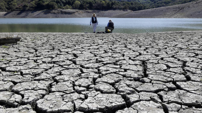 FILE - This March 13, 2014 file photo shows cracks in the dry bed of the Stevens Creek Reservoir in Cupertino, Calif. The Obama administration is more certain than ever that global warming is changing Americans' daily lives and will worsen — conclusions that scientists will detail in a massive federal report to be released Tuesday, May 6, 2014. (AP Photo/Marcio Jose Sanchez, File)
