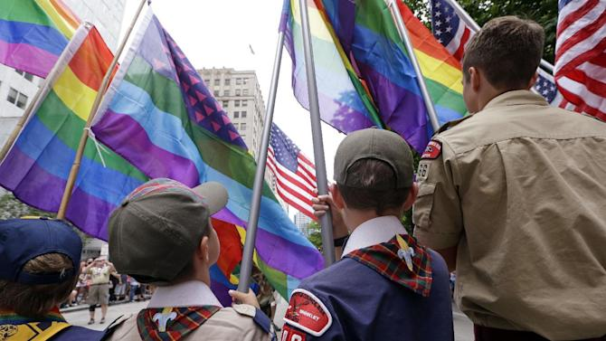 FILE - In this Sunday, June 28, 2015 file photo, Cub Scouts and Boy Scouts prepare to lead marchers while waving rainbow-colored flags at the 41st annual Pride Parade in Seattle, two days after the U.S. Supreme Court legalized gay marriage nationwide. On Monday, July 27, 2015, the Texas-based Boy Scouts of America ended its blanket ban on gay adult leaders but will allow church-sponsored Scout units to maintain the exclusion for religious reasons. (AP Photo/Elaine Thompson)