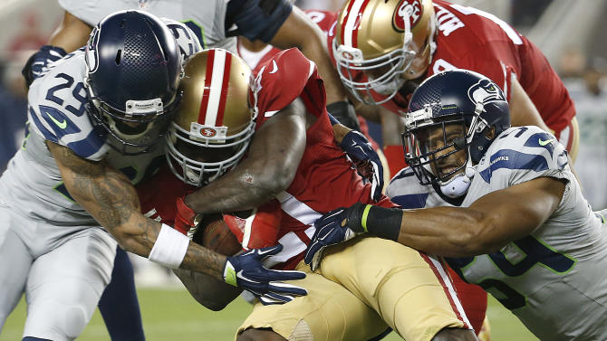 San Francisco 49ers running back Frank Gore, center, is tackled by Seattle Seahawks free safety Earl Thomas (29) and middle linebacker Bobby Wagner (54) during the first quarter of an NFL football game in Santa Clara, Calif., Thursday, Nov. 27, 2014. (AP Photo/Tony Avelar)