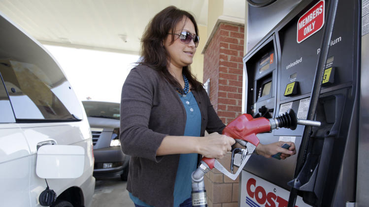 Myryam Adams, of Wesley Chapel, N.C., pumps gas at a Costco warehouse in Matthews, N.C., Tuesday, Nov. 8, 2011. Wholesale businesses in the U.S. reduced their stockpiles in September for the first time in nearly two years, while their sales rose. (AP Photo/Chuck Burton)