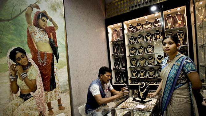 """In this Thursday Oct. 11, 2012 photo, a customer uses his calculator to convert  a jewelry price at a jewelry shop in the gold suq in Dubai, United Arab Emirates. Dubai is building itself up as a center for the gold trade, between the resources in Africa and consumers in the rising economies of China and India. """"There's no doubt the geographical location of Dubai has played an important factor,"""" said Malcolm Wall Morris, CEO of Dubai Multi Commodities Centre, that set up by the emirate to oversee the trade. (AP Photo/Kamran Jebreili)"""
