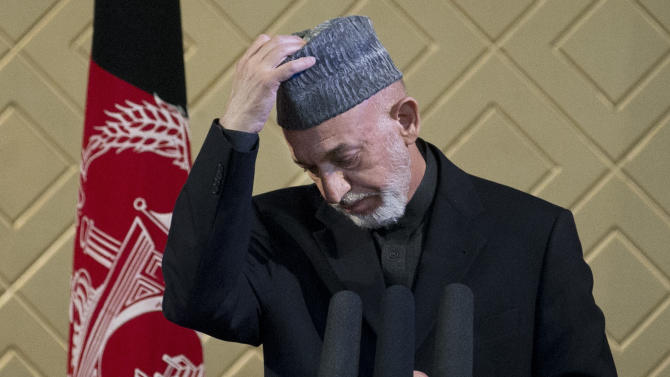 FILE - In this Thursday, May 9, 2013 file photo, Afghan President Hamid Karzai takes off his hat during a ceremony at Kabul University in Kabul, Afghanistan. Karzai was due in Qatar Sunday to discuss his country's stalled peace process and the possible opening of a Taliban office in the Gulf state, officials said. (AP Photo/Anja Niedringhaus, File)