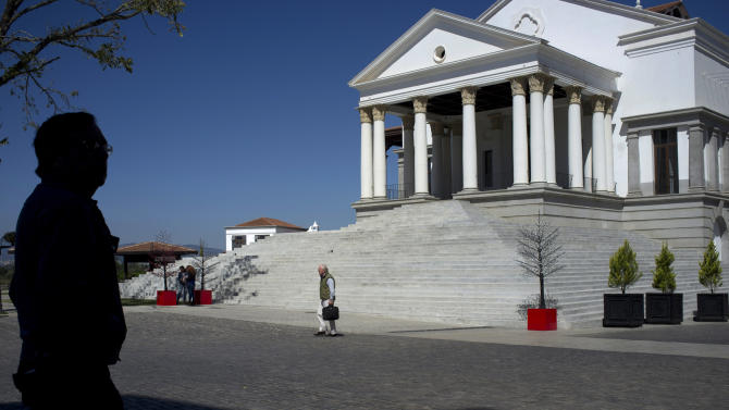 """In this Nov. 20, 2012 photo, people walk near the city hall in Paseo Cayala, a nearly independent city on the edges of Guatemala City. The city hall is at the center of the development, eventually to become """"Cayala City,"""" where the owners' association meets. As a part of the capital, Cayala City is governed by the same mayor and municipal authorities. (AP Photo/Moises Castillo)"""
