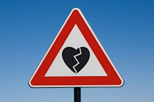Broken heart on a warning road signal.