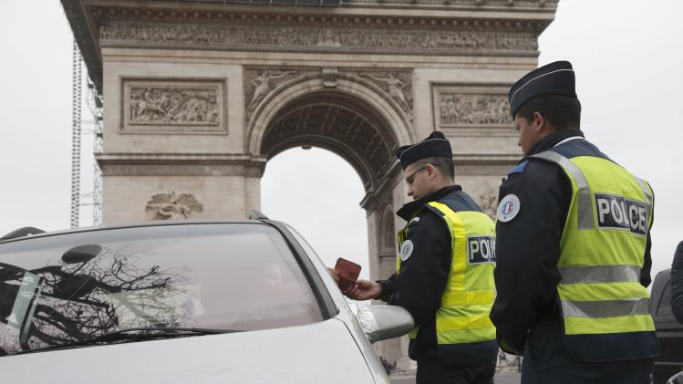 Police officers control cars with even-numbered licence plates which are not allowed to drive today, near the Arc de Triomphe in Paris