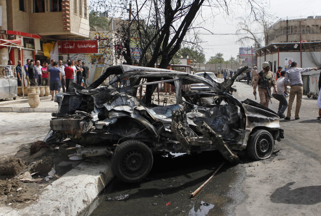 People gather at the scene of a car bomb attack close to one of the main gates to the heavily-fortified Green Zone, which houses major government offices and the embassies of several countries, includ
