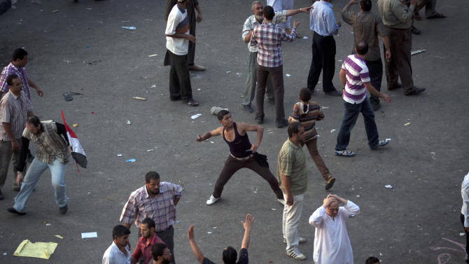A protester throws a stone after scuffles broke out between groups of protesters in Tahrir square when chants against the new Islamist president angered some in the crowd in Cairo, Egypt, Friday, Oct. 12, 2012. Thousands of supporters and opponents of Egypt's new Islamist president clashed in Cairo's Tahrir Square on Friday, hurling stones and concrete and swinging sticks at each other in the first such violence since Mohammed Morsi took office more than three months ago.(AP Photo/Khalil Hamra)