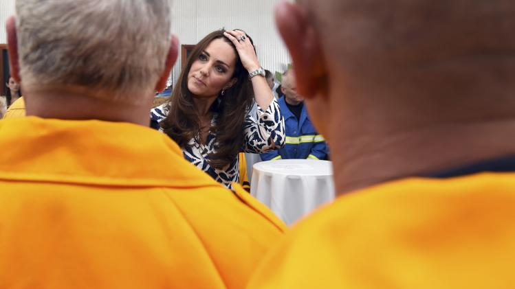 Catherine, the Duchess of Cambridge, talks with New South Wales Rural firefighters during a visit to the Blue Mountains suburb of Winmalee, that lost homes during bushfires last year, with her husband, Britain's Prince William, west of Sydney