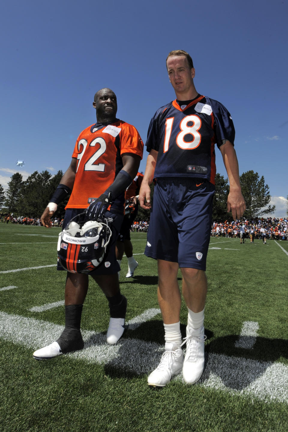 Denver Broncos quarterback Peyton Manning (18) and Elvis Dumervil (92) talks as the leave the practice field following the opening session of Denver Broncos NFL football training camp in Englewood, Colo., Thursday, July 26, 2012. (AP Photo/Jack Dempsey)