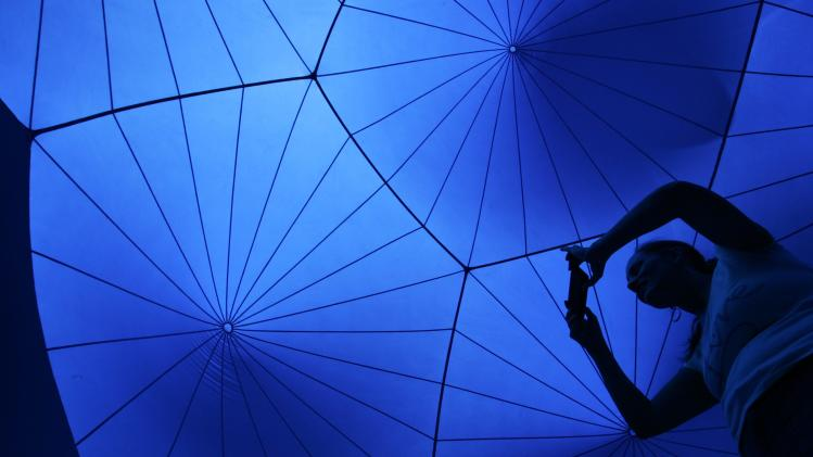 A woman takes a photograph inside Exxopolis, an inflatable walk-in luminarium at Grand Park in Los Angeles, California