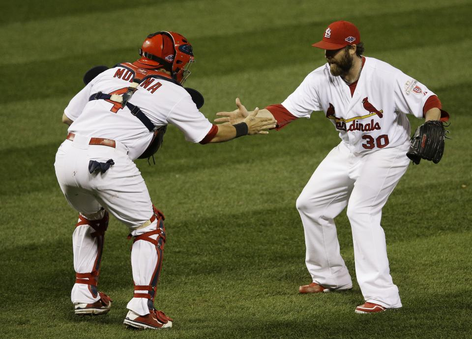St. Louis Cardinals relief pitcher Jason Motte (30) and St. Louis Cardinals catcher Yadier Molina (4) celebrate after the Cardinals beat the San Francisco Giants 3-1 in Game 3 of baseball's National League championship series Wednesday, Oct. 17, 2012, in St. Louis. (AP Photo/Patrick Semansky)
