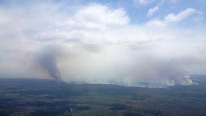 In this aerial photo provided by the New South Wales Rural Fire Service, plumes of smoke rises from a fire near Sussex Inlet, Australia, Wednesday, Jan. 9, 2013. Temperatures cooled from record highs across much of southern Australia on Wednesday, reducing the danger from scores of wildfires that have blazed for days.  (AP Photo/NSW Rural Fire Service) EDITORIAL USE ONLY
