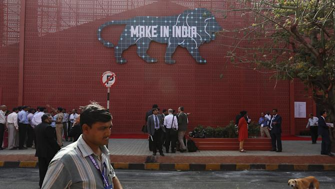 People stand outside before the inauguration at the exhibition centre of the 'Make In India' week in Mumbai