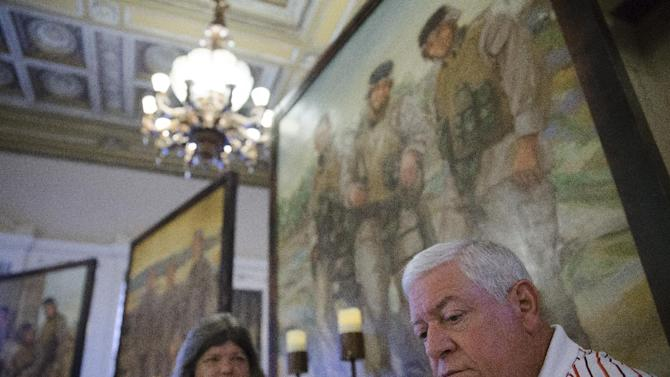 In this Tuesday, July 28, 2015 photo Ken Kreuter, alongside Pat Murray, pauses as he speaks of their son Marine Sgt. David Kreuter, likeness displayed top right, at the traveling Eyes of Freedom Lima Company Memorial currently displayed at the Cincinnati Masonic Center. Kreuter was one of 14 Marines from Ohio-based Lima Company who were killed by an IED explosion in Iraq 10 years ago. The memorial features full-length portraits of the fallen members of Lima Company. (AP Photo/John Minchillo)