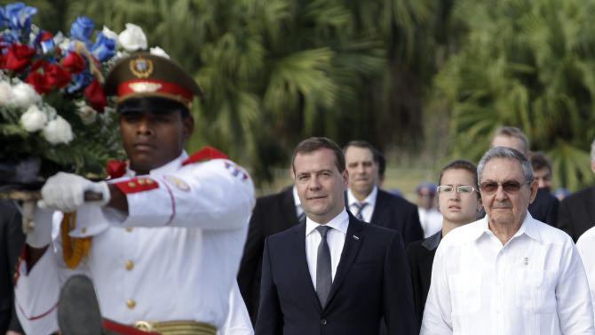 Cuba's President Raul Castro, right, and Russia's Prime Minister Dmitry Medvedev, center, attend a wreath-laying ceremony at the Internationalist Soviet soldier mausoleum in Havana, Cuba, Friday, Feb. 22, 2013. (AP Photo/Franklin Reyes)