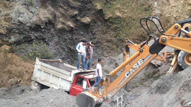 Residents use heavy equipment to look for people feared buried at a sand mine, after a magnitude 7.4 earthquake struck in San Marcos, Guatemala, Wednesday Nov. 7, 2012. The mountain village, some 80 miles (130 kilometers) from the epicenter, suffered much of the damage with some 30 homes collapsing in its center. There are three confirmed dead and many missing after the strongest earthquake to hit Guatemala since a deadly 1976 quake that killed 23,000. (AP Photo/Moises Castillo)