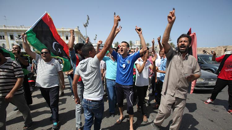 Libyans hold up their ink-marked fingers that shows they have voted as they celebrate in Martyrs' Square in Tripoli, Libya, Saturday, July 7, 2012. Jubilant Libyan voters marked a major step toward democracy after decades of erratic one-man rule, casting their ballots Saturday in the first parliamentary election after last year's overthrow and killing of longtime leader Moammar Gadhafi. But the joy was tempered by boycott calls, the burning of ballots and other violence in the country's restive east. (AP Photo/Abdel Magid Al Fergany)
