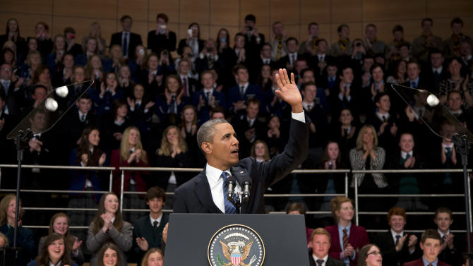 President Barack Obama waves as he arrives to deliver a speech at the Belfast Waterfront Hall on Monday June 17, 2013, in Belfast, Northern Ireland. Obama is attending the G-8 summit in Enniskillen, Northern Ireland where leaders are expected to discuss the ongoing conflict in Syria, and free-trade issues. (AP Photo/Evan Vucci)