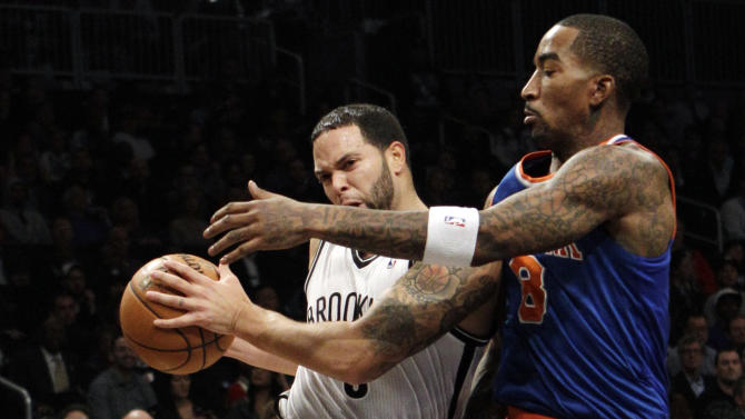 Brooklyn Nets guard Deron Williams (8) drives against New York Knicks guard J.R. Smith (8) in the first half of their NBA basketball game at Barclays Center, Monday, Nov. 26, 2012, in New York. (AP Photo/Kathy Willens)