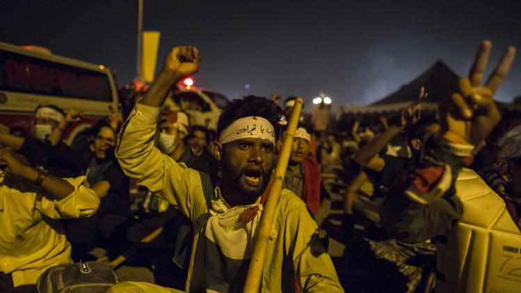 """A supporter of Qadri, leader of the PAT political party, chants slogans in front of the Parliament house building during """"Revolution March"""" in Islamabad"""