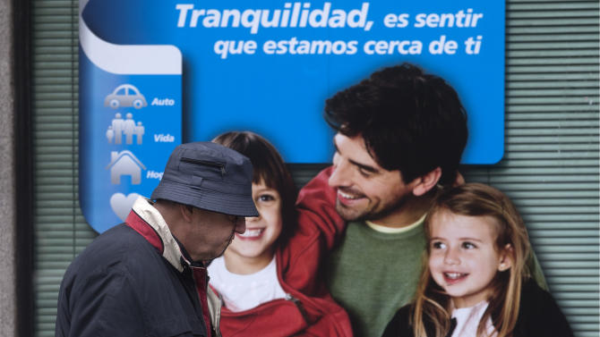 A man walks past a poster in a bank window showing a smiling family with a message reading 'Tranquility is to feel that we are close to you'  in Madrid, Spain, Friday April 26, 2013.  The Spanish Government is to announce new round of reforms Friday that could include new cutbacks to meet deficit target.(AP Photo/Paul White)