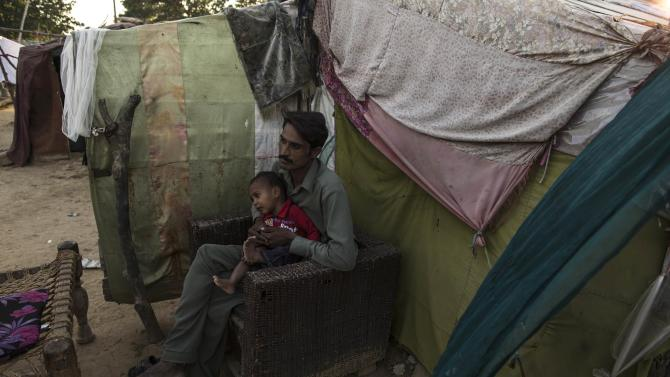 A man, whose family moved to Islamabad from Sargodha in Punjab Province to look for work, sits beside his relatives makeshift shelter in Islamabad