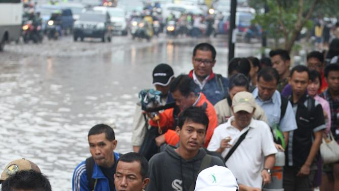 People wade through a flooded street in Jakarta, Indonesia Friday, Jan. 18, 2013.  Indonesia's army deployed rubber boats in the capital's business district on Thursday to rescue people trapped in floods that inundated much of the city of 14 million people.(AP Photo/Achmad Ibrahim)