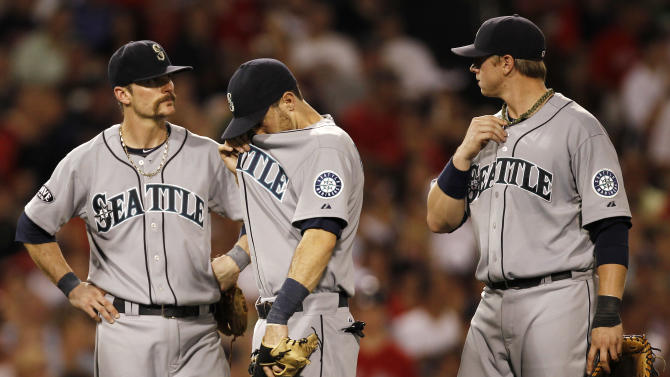 Seattle Mariners infielders Brendan Ryan, left, Dustin Ackley, center, and Justin Smoak wait for a pitching change during the seventh inning of a baseball game against the Boston Red Sox at Fenway Park in Boston, Friday, July 22, 2011. (AP Photo/Winslow Townson)