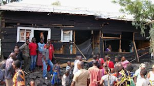 Onlookers gather around a house damaged by overnight …