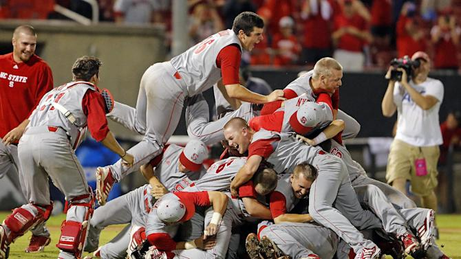 North Carolina State's Carlos Rodon (16) jumps on top of teammates as they celebrate their 5-4 win over Rice in the 17th inning of an NCAA college baseball tournament super regional game, Sunday, June 9, 2013, in Raleigh, N.C. (AP Photo/Karl B DeBlaker)