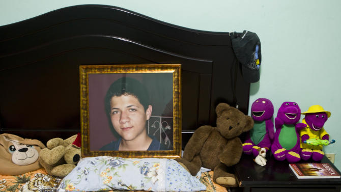 In this Oct 17, 2012 photo, an image of late Jaasiel Yanez, 15, sits on his bed at his parent's home in Tegucigalpa, Honduras. According to his relatives, Jaasiel was killed by soldiers early Sunday, May 27, when he was riding a motorcycle, near a military checkpoint, allegedly accompanied by a young woman.  (AP Photo/Esteban Felix)