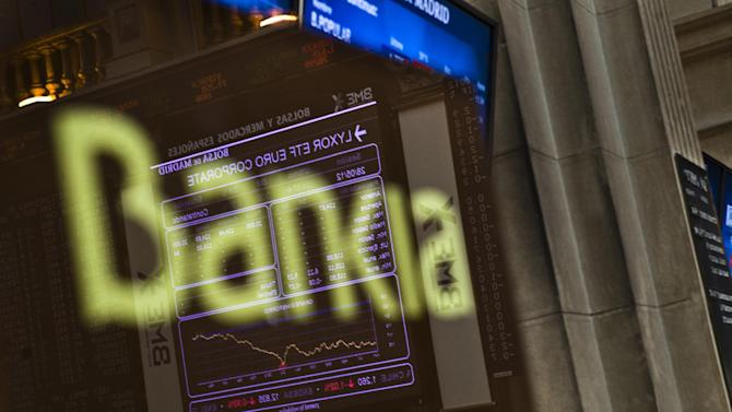 FILE - In this May 28, 2012 file photo, the Stock Exchange main display is reflected on a Bankia sign in Madrid. Shares of Spain's bailed-out bank Bankia plunged 13 percent on Thursday Dec. 27, 2012 after officials with the nation's bank bailout fund revealed the nationalized institution had a negative value of euro 4.2 billion ($5.6 billion). Bankia was formed in 2010 in a merger of seven unlisted Spanish savings banks whose heavy lending for property hurt them badly after the country's extended real estate boom collapsed in 2008. (AP Photo/Daniel Ochoa de Olza, File)