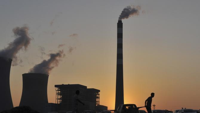 A worker pulls a cart in front of the smoking chimneys of a power plant in Hefei