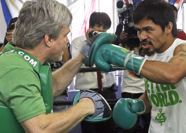 Manny Pacquiao, of the Philippines, spars with his trainer Freddie Roach at a media workout in preparation for his upcoming boxing match against Timothy Bradley, at Roach&#39;s Wild Card Boxing Club in Los Angeles Wednesday, May 30, 2012. Pacquiao will be defending his World Boxing Organization (WBO) welterweight championship crown against WBO junior welterweight champion Bradley at the MGM Grand Garden Arena in Las Vegas Saturday, June 9. (AP Photo/Reed Saxon)
