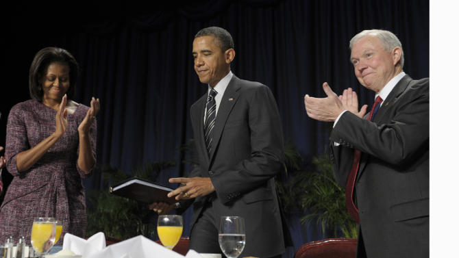President Barack Obama is applauded by first lady Michelle Obama and Sen. Jeff Sessions, R-Ala. after speaking at the National Prayer Breakfast in Washington, Thursday, Feb. 2, 2012. (AP Photo/Susan Walsh)