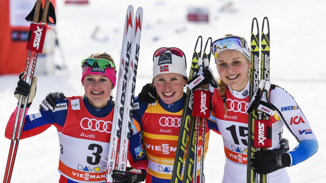 Norway's third placed Ingvild Flugstad Oestberg, Norway's winner Marit Bjoergen and second placed Stina Nilsson of Sweden, from left, pose for the media after the women's 1.3 km sprint final run at the Cross Country World Cup in Davos, Switzerland, Sunday, Dec. 21, 2014. The event has been moved from La Clusaz, France, due to lack of snow. (AP Photo/Keystone, Gian Ehrenzeller)