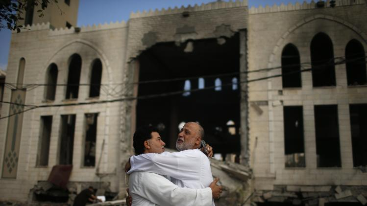 Palestinians reacts in front of a mosque which witnesses said was hit in an Israeli air strike, in Gaza City